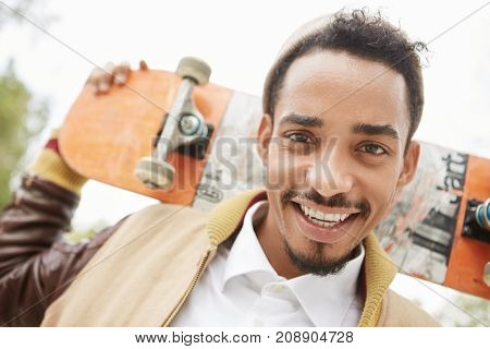 Skateboarding, Sport, Hobby And Recreation Concept. Relaxed Smiling Mixed Race Bearded Teenager Hold