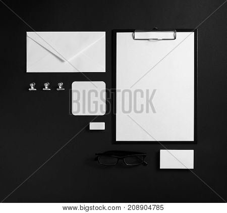 Photo of blank stationery set. Corporate identity template on black paper background. Mock up for placing your design. Responsive design mockup. Top view.