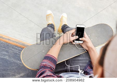 Modern Smart Phone With Blank Screen In Hands Of Talented Skateboarder. Young Hipster Guy Or Skater