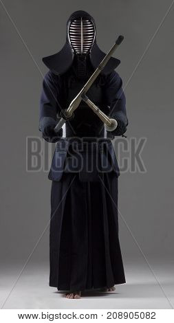 Portrait of man kendo fighter with  two bamboo swords in traditional uniform . Shot in studio.