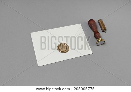 Blank envelope with wax seal and stamp on gray paper background.