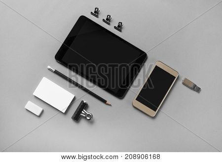 Blank stationery and gadgets at gray paper background. Top view.