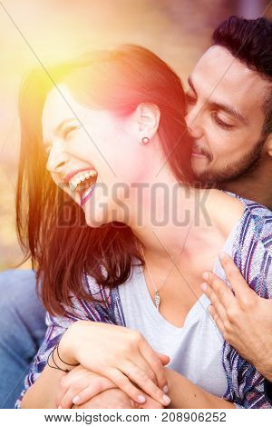 young beautiful couple sitting outside in Park and hugging each other