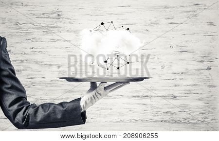 Cropped image of waitress's hand in white glove presenting cloud with social media network structure on metal tray. Gray wall on background. 3D rendering.
