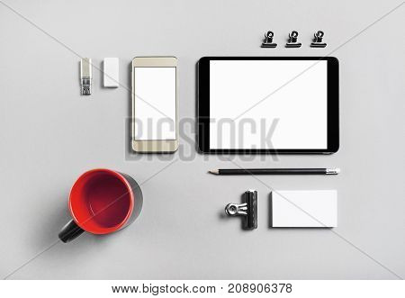 Smartphone tablet and blank stationery on gray paper background. Brand ID template for placing your design. Top view.
