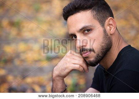 handsome young man sitting outside on train tracks and looking pensive