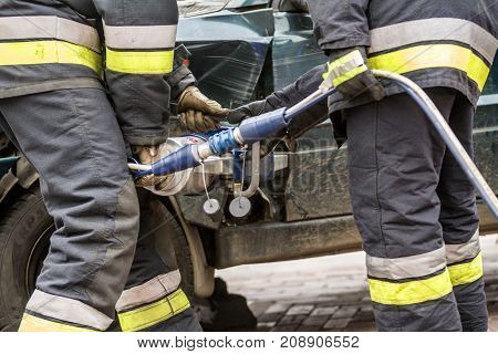 Firefighters working on an auto vehicle extrication with a hydraulic power rescue tool