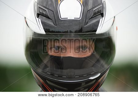 Close up shot of blue eyed Caucasian male wearing stylish motorcycle helmet staring at camera with confident determined look before race. People extreme sports active lifestyle speed and adrenalin