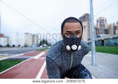 Athletic excellence. Close up shot of handsome young dark-skinned male runner about to start his run on track field using training mask to get better results while exercising outdoors in the morning