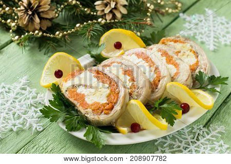 Festive snack on Christmas table. Homemade roll of mackerel with carrots and eggs in gelatin. Decorated Christmas tree branches. Sliced pieces of roll are served with lemon cranberries and parsley
