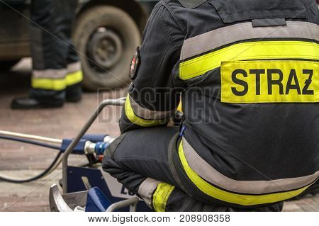ZAMOSC/POLAND -AUGUST 13,2017: Firefighters working on an auto vehicle extrication with a hydraulic power rescue tool. Letters STRAZ means Firefighter.