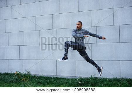Freeze action shot of sturdy healthy young African American male athlete in trendy sportswear doing high jumps outdoors at blank grey wall. Strenght power endurance determination and stamina