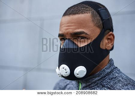 Breathing technologies for fitness and sport. Portrait of young muscular Afro American sportsman wearing respiratory resistance device to strengthen breathing muscles and improve breathing mechanics