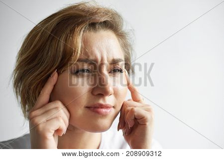 Close up shot of frustrated stressed out young woman student or employee having painful look holding fingers on her temples suffering from migraine or headache. Negative human facial expressions