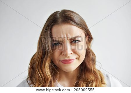 Negative human emotions and feelings. Picture of displeased grumpy young woman posing at blank studio wall frowning eyebrows her look and grimace expressing anger annoyance and irritation