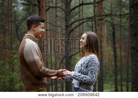 Side view of happy romantic young couple holding hands looking into each other's eyes and smiling joyfully standing among trees in autumn forest: guy declaring his love for his charming girlfriend