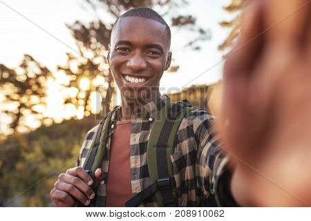 Smiling young African man wearing a backpack taking a selfie while hiking alone up a trail on a sunny day