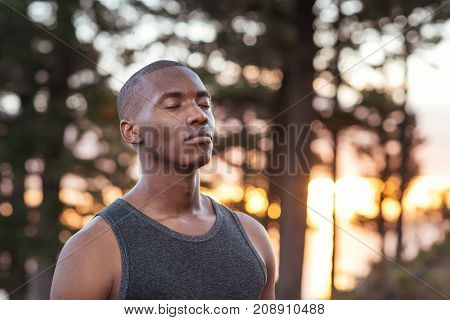 Young African man standing alone on a trail in the forest getting focused for a cross country run
