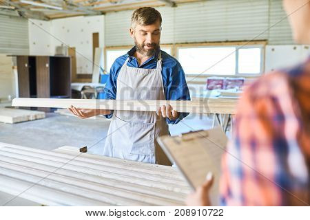 Portrait of skilled carpenter evaluating piece of wood in workshop, choosing best materials