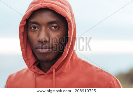 Portrait of a focused young African man in a hoodie standing with his eyes closed on a trail by the ocean preparing for a run