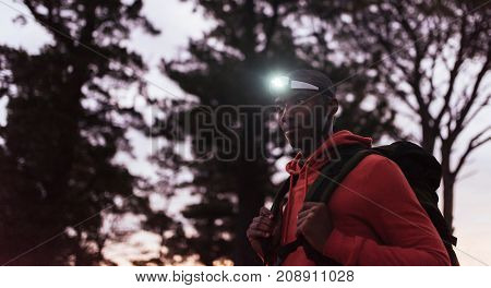 Focused young African man wearing a headlamp standing alone in the forest while out for a cross country run at dusk
