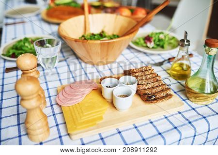 High angle  of delicious wholesome food on rustic table over gingham blue tablecloth: sandwiches and  green salad in wooden bowl