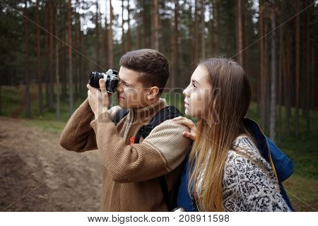 People trekking photography active lifestyle hobby and leisure. Talented young male photographer taking pictures of beautiful autumn wild nature while hiking in woods together with his girlfriend