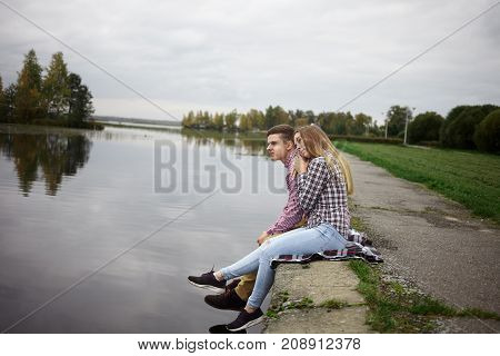 Love tenderness romance feelings and togetherness concept. Beautiful young Caucasian man and woman in love sitting on river bank and hugging feeling happy and relaxed away from city life