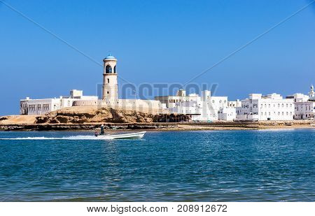 View on Sur Lighthouse with fisherman boat passing - Sur, Oman