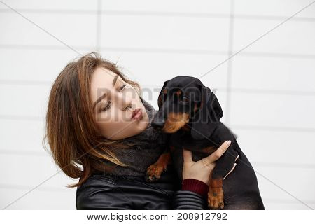 poster of Portrait of stylish responsible caring young European female dog owner is about to kiss her loyal devoted dachshund pet expressing her love and care to her four legged friend during nice walk
