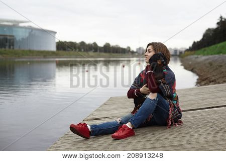 Outdoor portrait of beautiful young European female dog owner wearing red sneakers and ripped jeans relaxing on the riverside hugging her dachshund enjoying warm peaceful morning. People and animals