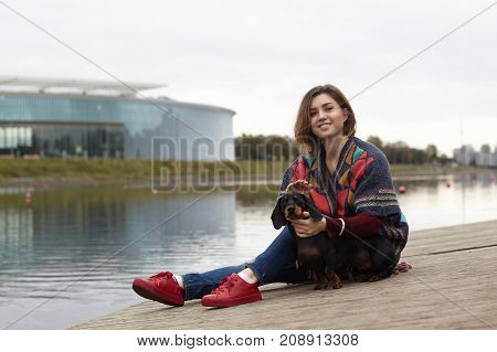 Lifestyle picture of happy attractive young woman with pierced nose sitting on embankment by the river with her lovely dachshund dog stroking its head and looking at camera with joyful smile