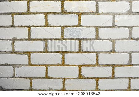 Texture Of An Old White Brick Wall With Building Seams Covered By Yellow Lichen