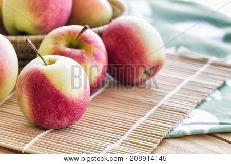 Stack of fuji apple on bamboo mat and in basket put on wood table for background or wallpaper.Delicious sweet and juicy fuji apple suitable for salad cooking or bakery.Fuji apple has origins in Japan. Apple fuji on table selective focus.