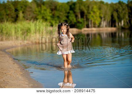 beautiful girl in a dress walking along the shore of the lake and having fun