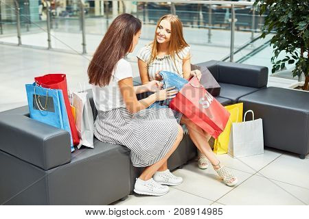 Portrait of two young women in shopping mall sitting on couch surrounded by paper bags, smiling happily discussing purchases bought on Sale
