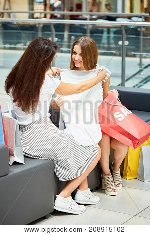 Portrait of two young women in shopping mall surrounded by paper bags, chatting happily discussing clothes bought on Sale