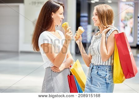 Side view portrait of two beautiful girls shopping in mall, chatting happily holding paper bags and eating ice cream