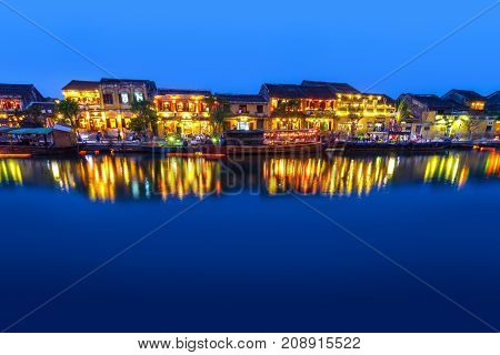 Hoi An Vietnam riverside cafes shops and boats just after sunset.