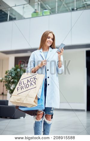 Portrait of happy young woman shopping on Black Friday holding smartphone and paper bags with purchases