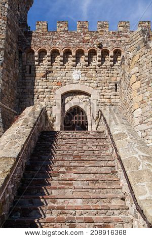 Brick and rock stairs leading up to a gated entrance of a castle in the morning sunshine with blue sky.