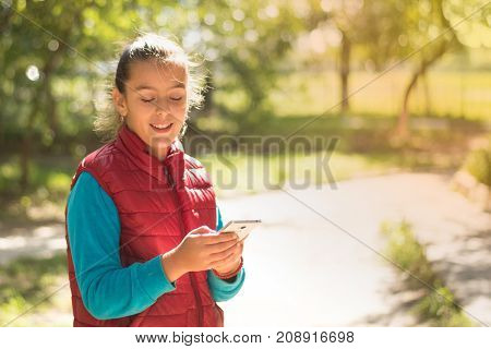 Beautiful girl talking on a smartphone in a red vest on the outdoor.Handsome smiling girl with mobile phone walking on outdoor. Young caucasian girl receiving good news by phone. Portrait smiles girl