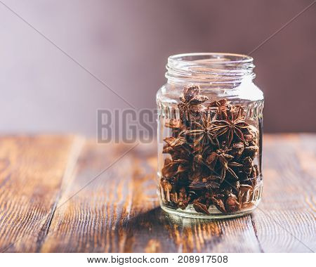 Jar of Star Anise on Wooden Table. Copy Space on the Left.