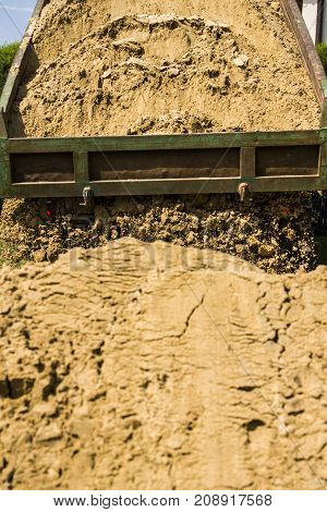Truck dumps its load of sand on costruction site