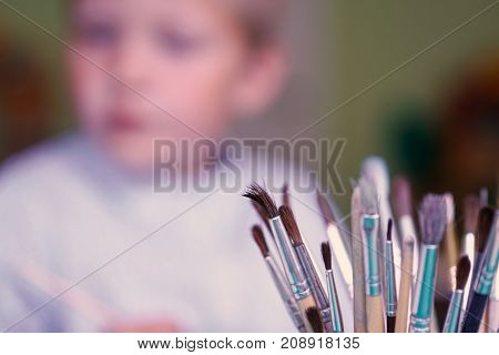 A lot of brushes for drawing and a little boy in the background. School education concept.