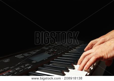 Hands of musician playing the synth on a black background