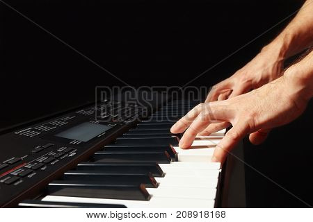 Hands of musician playing the electronic organ on a black background