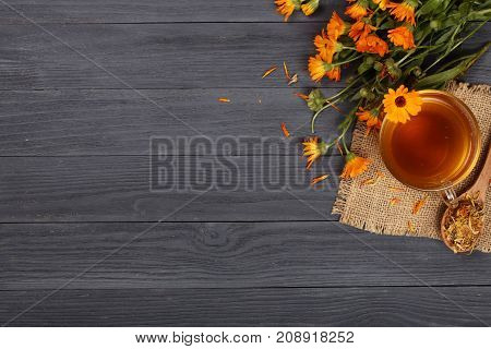 Calendula tea with fresh and dried flowers on black wooden background with copy space for your text. Top view.