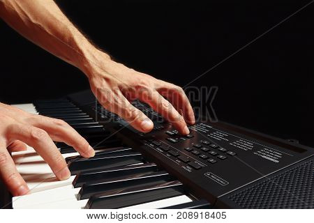 Hands of pianist play the keys of the synth on a black background