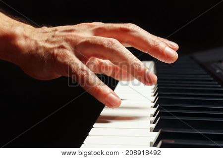 Hand of pianist play the keys of the digital piano on a black background close up